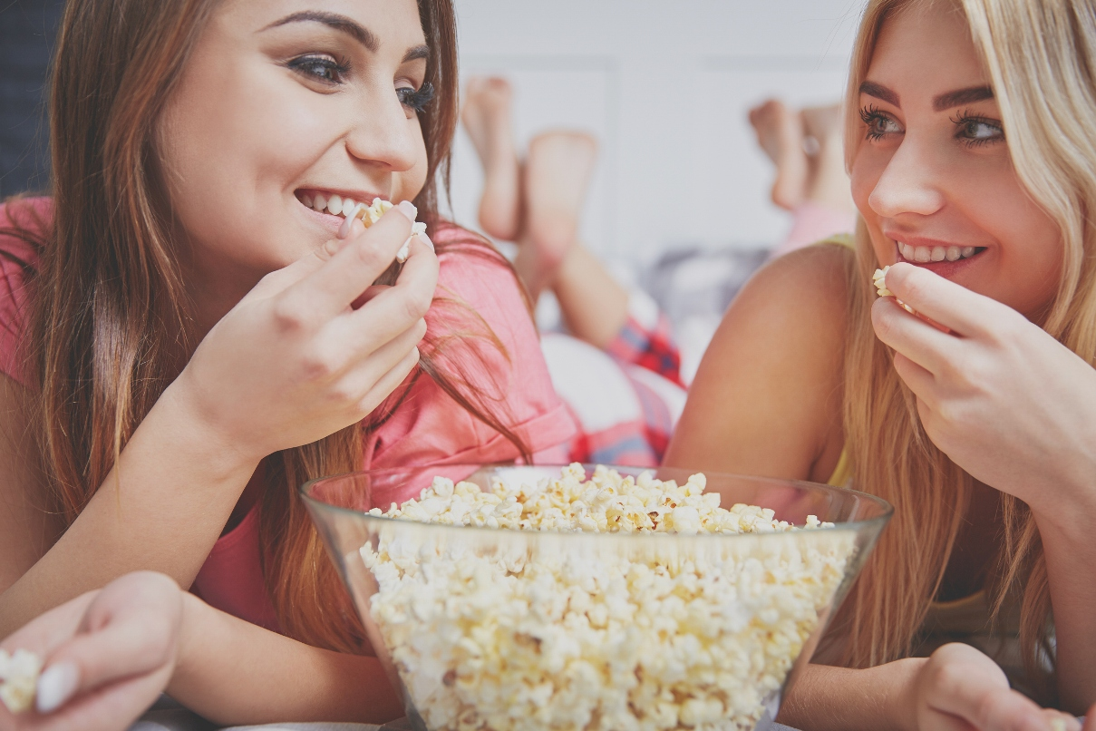 two friends, talking, smiling, and eating popcorn