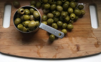 pitted green olives on a wood board