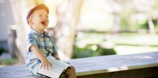 little boy sitting on a bench, holding a book, and laughing