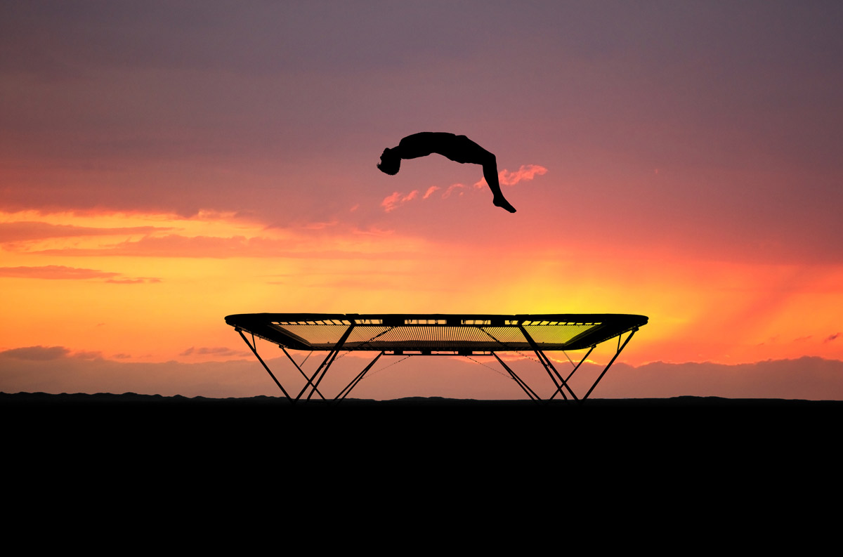 athlete flying above a trampoline with sunset in the background