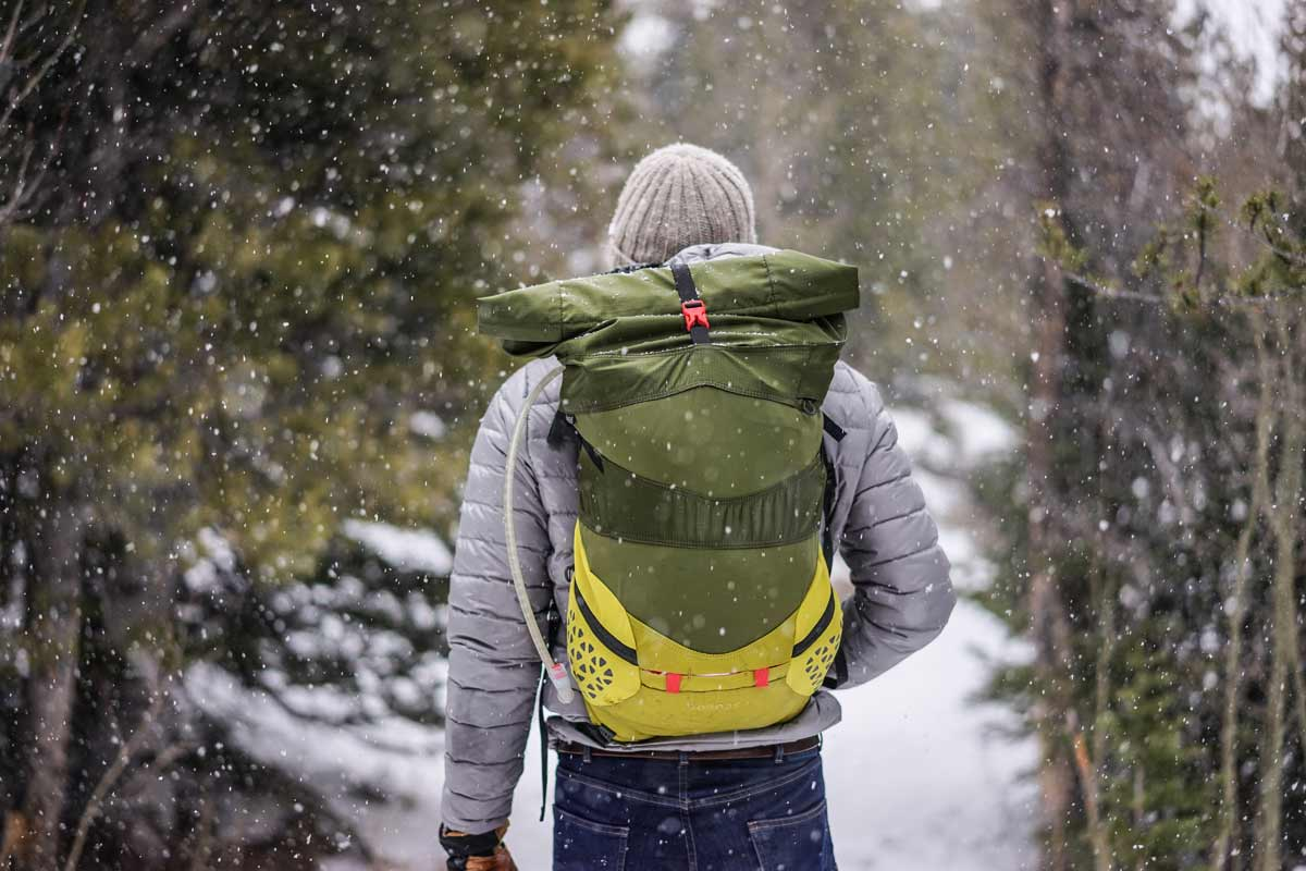 man with hiking gear walking in snow