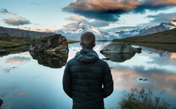 Man standing in a beautiful nature scene with the sky, rock formations, and a lake