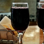 two glasses of red wine with a basket of bread and a glass of ice water