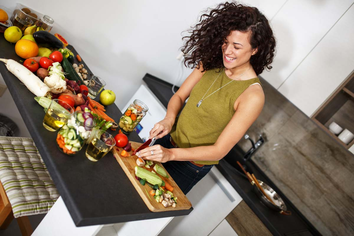 happy woman cutting produce on a cutting board