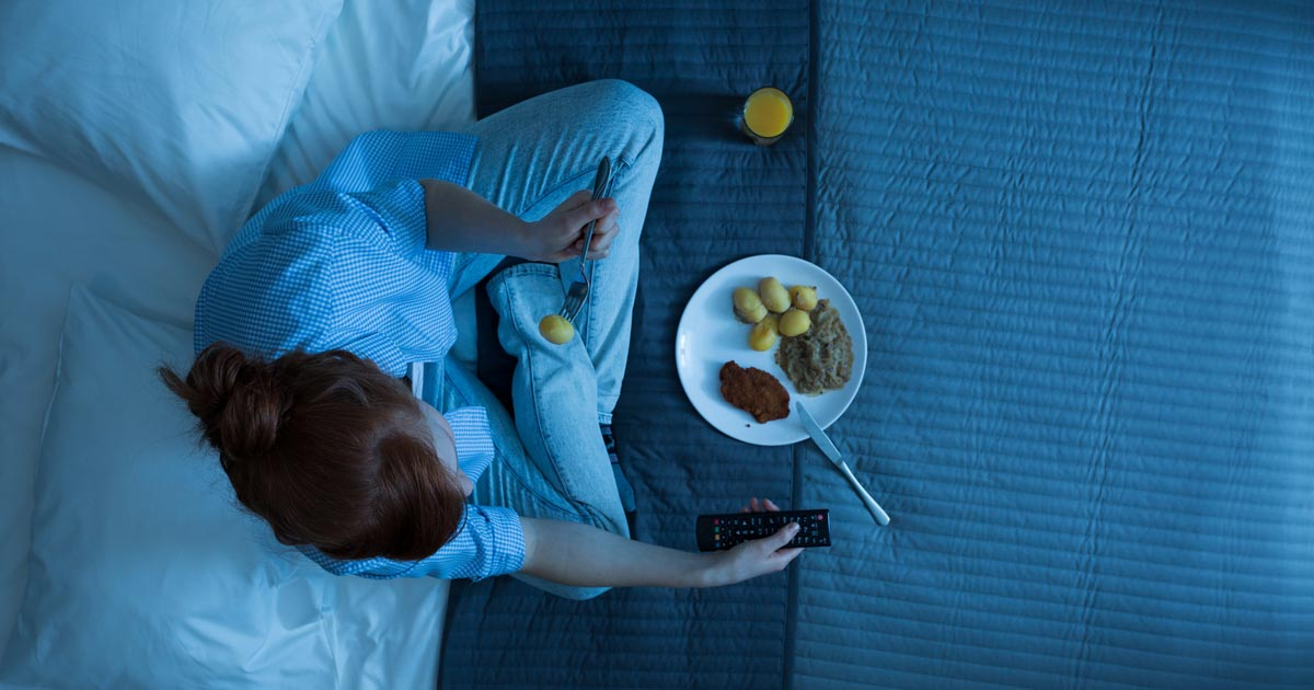 topdown view of woman sitting on bed, eating, and watching tv
